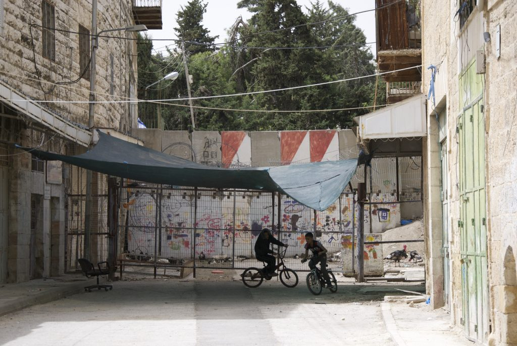 Children cycle in the gaze of Israeli soliders by the wall which cuts Hebron in two